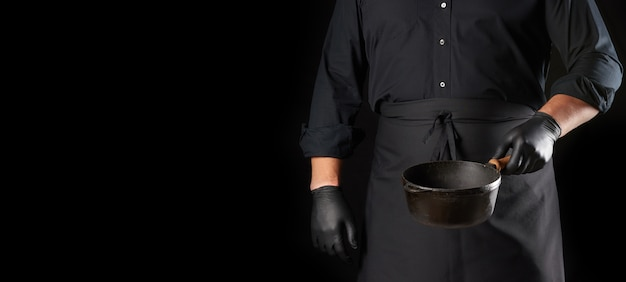 Cuire En Uniforme Noir Et Des Gants Détient Une Casserole En Fonte Vintage Ronde Vide Photo Premium