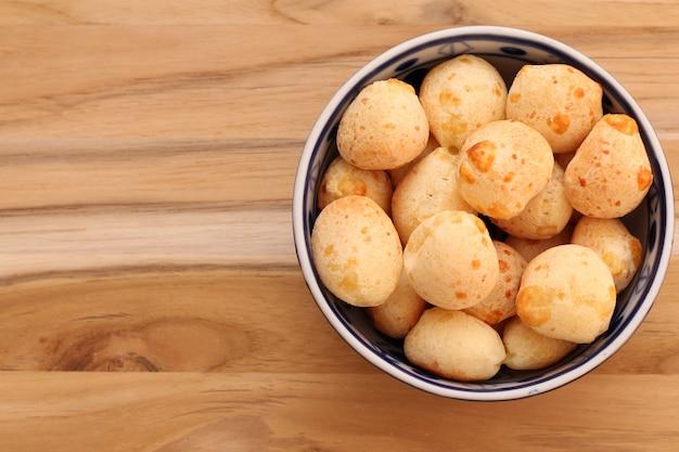 Cuisine et boissons brésiliennes - bol à pain au fromage traditionnel (pão de queijo) sur une table en bois Photo Premium