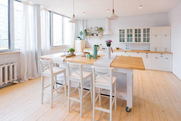 Cuisine élégante Aux Couleurs Claires Dans Un Appartement Duplex Moderne Et Branché Avec De Grandes Fenêtres Hautes. Photo Premium