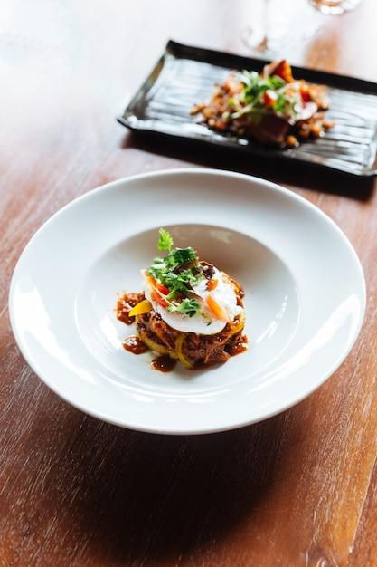 Cuisine fusion: canape de hamburger au bœuf recouverte d'œuf poché, de tomate et de coriandre. Photo Premium