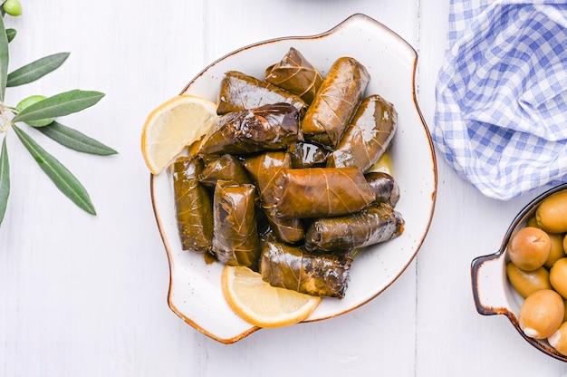 Cuisine grecque traditionnelle. riz enveloppé dans des feuilles de vigne. dolma au citron et aux épices. plats cuisinés à la maison Photo Premium