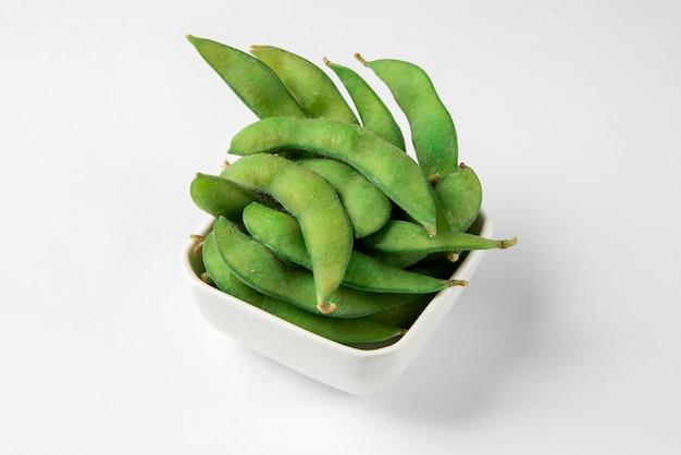 Cuisine Japonaise Edamame Cuit à La Vapeur Fraîche Ou Fèves De Soja Vertes Dans Le Bol Blanc Sur La Surface Blanche. Photo Premium