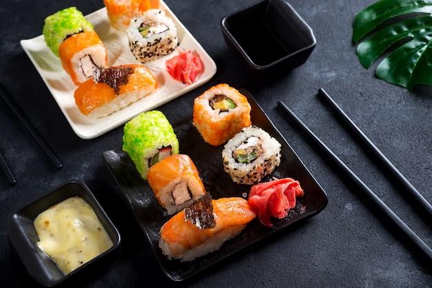 Cuisine japonaise - sushi, petits pains, baguettes, sauce soja sur fond noir Photo Premium