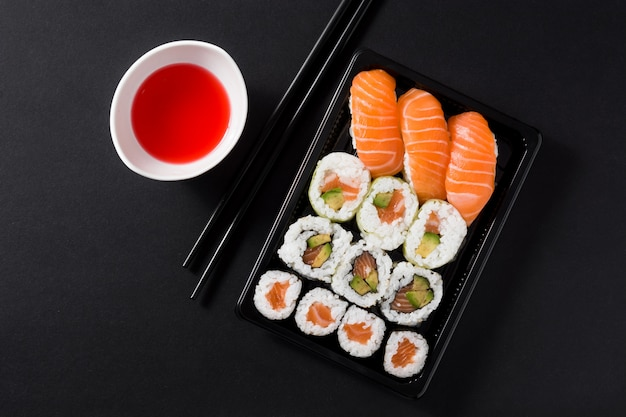 Cuisine japonaise: sushis maki et nigiri sur fond noir, vue de dessus Photo Premium