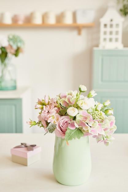 Cuisine lumineuse dans le style de la provence, sur la table des plats et un bouquet de fleurs dans un vase Photo Premium