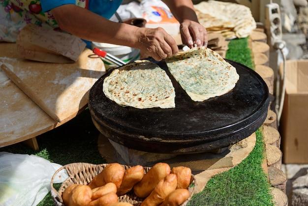 Cuisine nationale azerbaïdjanaise - kutabs en préparation. gutab alevins en feu Photo Premium