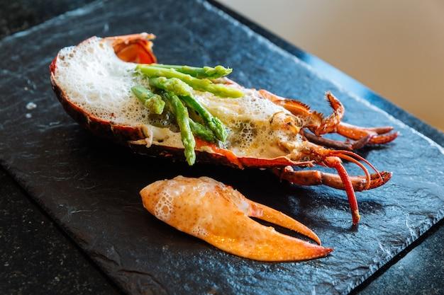 Cuisine raffinée: chair de homard et pince recouverte de mousse aux asperges servie sur une assiette en pierre. Photo Premium