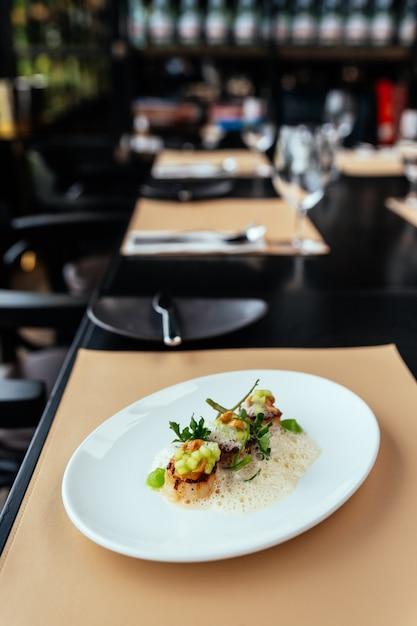 Cuisine raffinée créative: pétoncles d'hokkaido au velouté de pomme verte, de noisette et de coquillages. Photo Premium