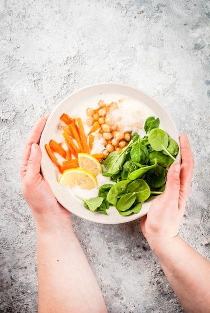 Cuisine végétalienne moderne, bol de yaourt salé avec haricots, pois chiches, épinards, carottes épicées, bol de yaourt au citron Photo Premium