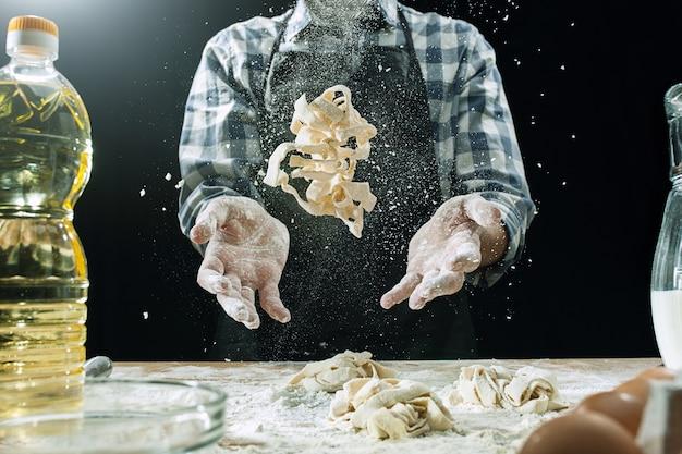 Cuisinier Masculin Professionnel Arrose La Pâte Avec De La Farine, Prépare Ou Cuit Du Pain à La Table De La Cuisine Photo gratuit