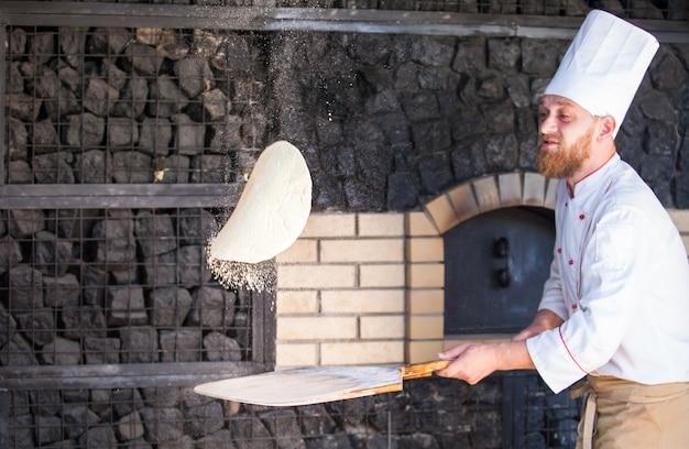 Cuisinier préparant une pizza dans un restaurant. Photo Premium