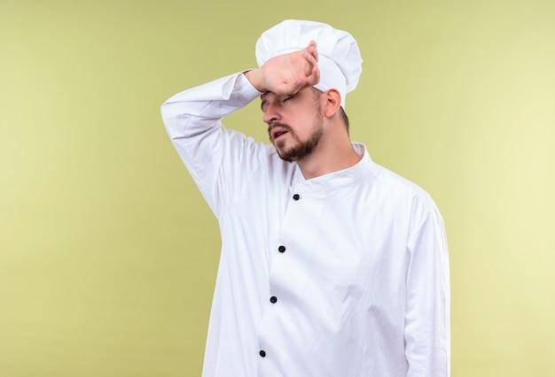 Cuisinier Professionnel Masculin En Uniforme Blanc Et Chapeau De Cuisinier à La Fatigue Et Surmené En Touchant Sa Tête Debout Sur Fond Gree Photo gratuit