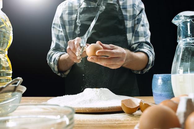 Un Cuisinier Professionnel Saupoudre La Pâte Avec De La Farine, Des Préparations Ou Cuit Du Pain Ou Des Pâtes à La Table De La Cuisine Photo gratuit