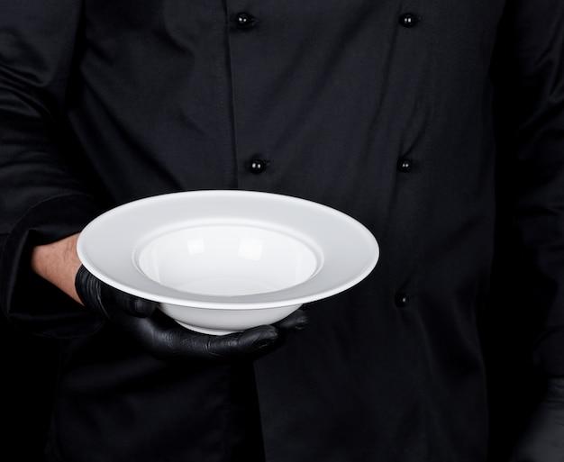 Cuisinier en uniforme noir et gants en latex noir tient dans sa main une assiette blanche vide ronde Photo Premium