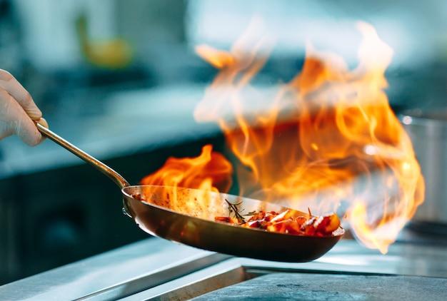 Les Cuisiniers Préparent Les Repas Sur Le Feu Dans La Cuisine Du Restaurant Ou De L'hôtel. Photo Premium