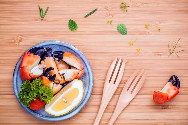 Cuisse de crabes rouges cuits à la vapeur dans un bol avec des ingrédients sur une planche à découper boisée. Photo Premium