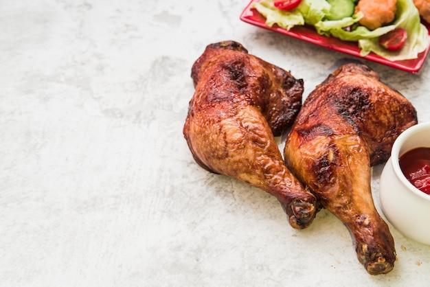 Cuisse de poulet rôti avec sauce et salade sur fond de béton Photo gratuit