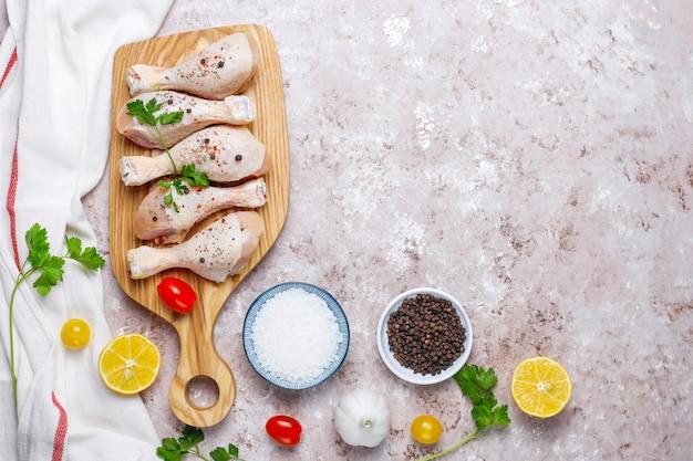 Cuisses De Poulet Aux épices Et Sel Prêts à Cuire Sur Une Planche à Découper. Photo Premium