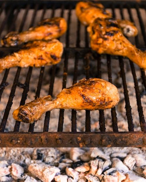Cuisses de poulet brillantes grillées sur le gril chaud Photo gratuit