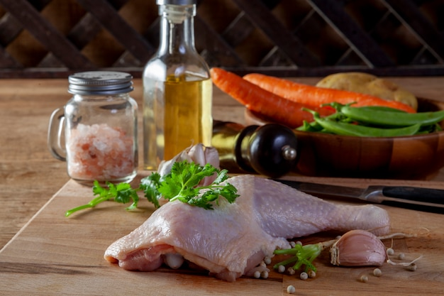 Cuisses de poulet crues avec des épices et des légumes sur une planche de bois Photo Premium