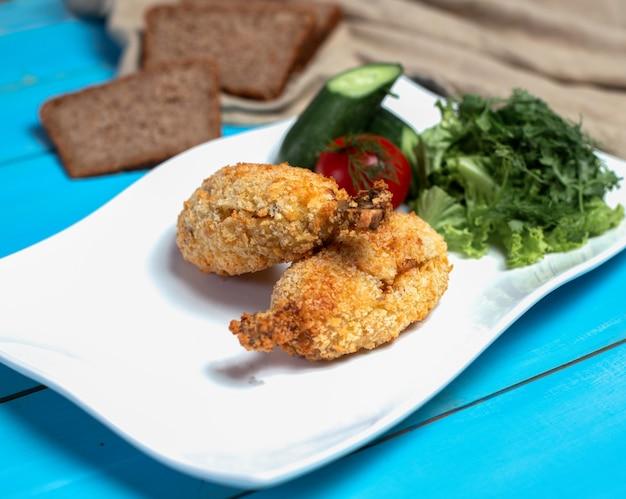 Cuisses de poulet frites croustillantes avec salade verte. Photo gratuit