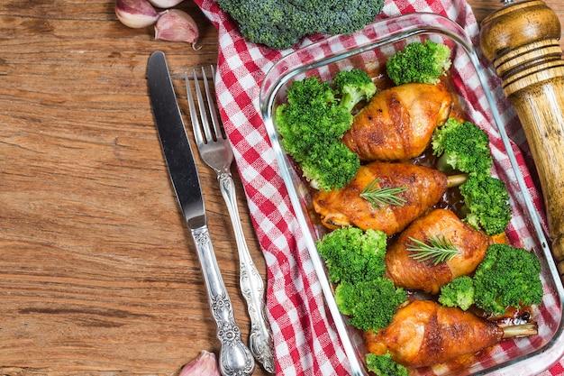 Cuisses de poulet avec des légumes sur une table en bois. Photo Premium