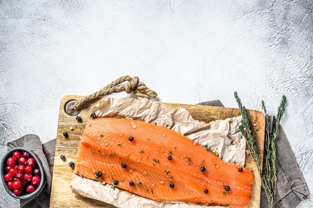 Cuisson Du Filet De Saumon Salé Sur Une Planche à Découper En Bois Avec Des Herbes Et Des épices. Fond Gris Photo Premium