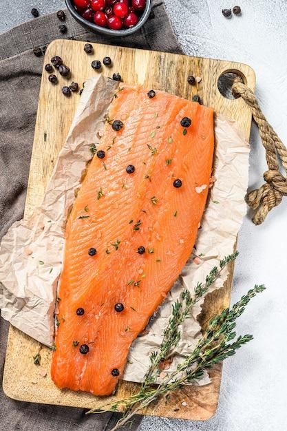 Cuisson Du Filet De Truite De Mer Salée Sur Une Planche à Découper En Bois Avec Des Herbes Et épices Photo Premium