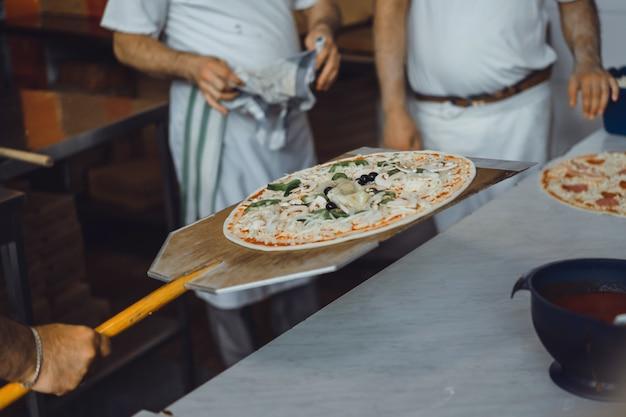 Cuisson grosse pizza Photo gratuit