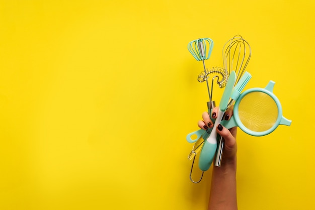 Cuisson à plat poser. mains féminines tenant des ustensiles de cuisine, tamis, rouleau à pâtisserie, spatule et bruch sur fond jaune. bannière avec espace de copie Photo Premium