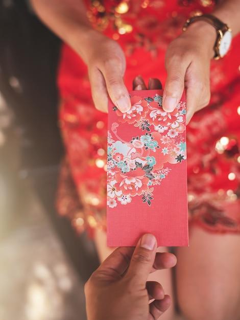 Culture chinoise dans le nouvel an chinois, les gens vont donner une enveloppe rouge. Photo Premium
