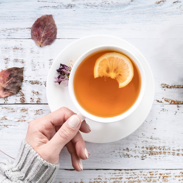 Culture femme tenant une tasse de thé sur une surface minable Photo gratuit