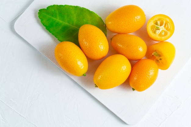 Cumquat ou kumquat avec une feuille verte sur un fond en bois blanc. Photo Premium