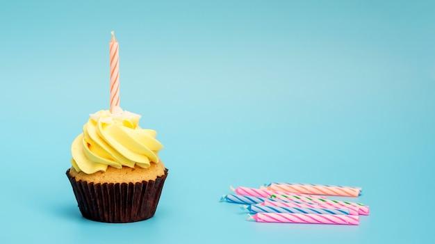 Cupcake et bougie sur un fond bleu. Photo Premium