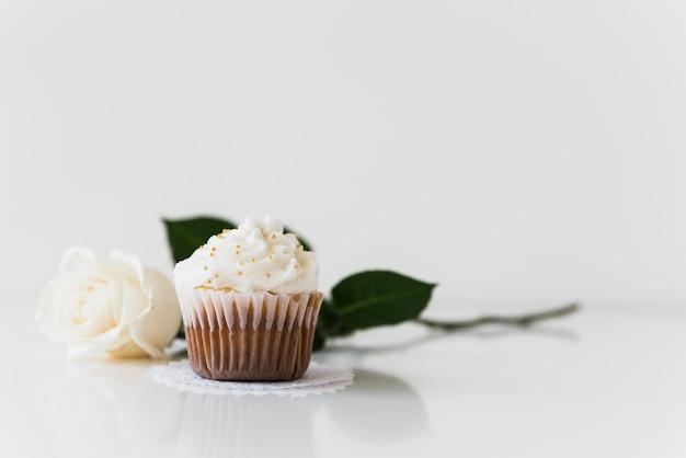 Cupcake coloré sur napperon avec rose sur fond blanc Photo gratuit