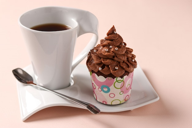 Cupcake à La Crème Au Chocolat Et Une Tasse De Café Disposés Sur Un Rose Photo Premium