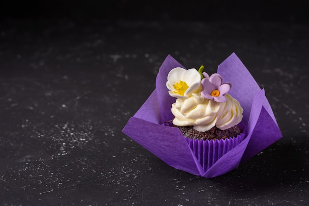Cupcake dans une enveloppe pourpre sur le dessus de table en pierre sombre. concept minimal. espace de copie. Photo Premium