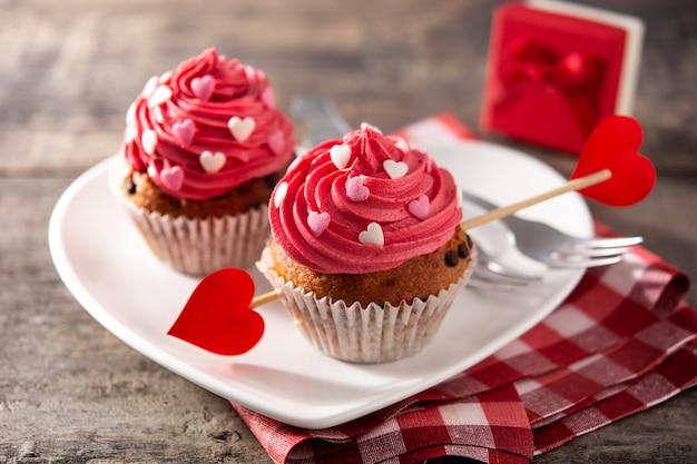 Cupcake Décoré De Coeurs De Sucre Et D'une Flèche De Cupidon Pour La Saint Valentin Sur Table En Bois Photo Premium