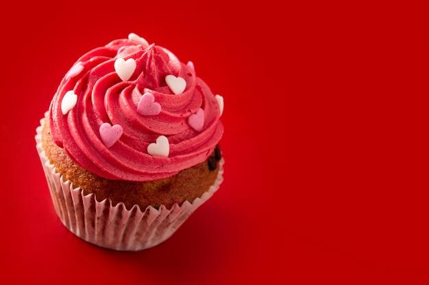 Cupcake Décoré De Coeurs De Sucre Pour La Saint-valentin Sur Fond Rouge Photo Premium