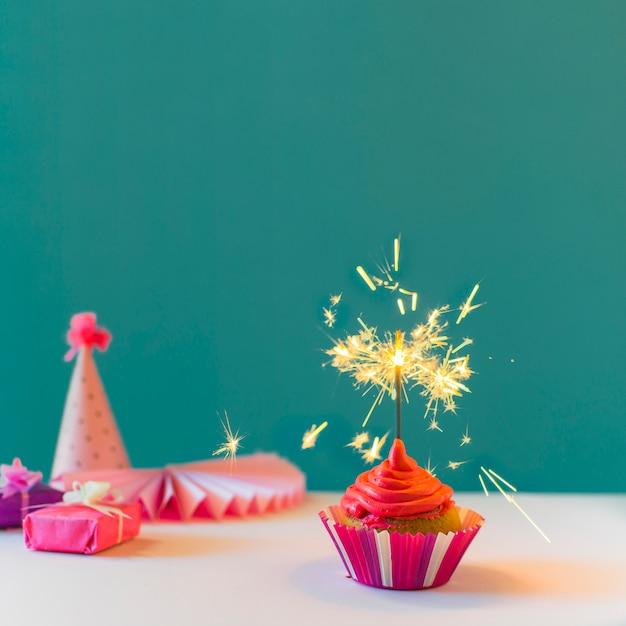 Cupcake avec sparkler brûlant sur fond vert Photo gratuit