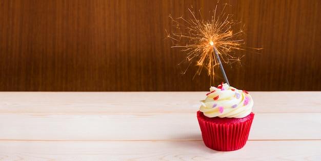 Cupcake de velours rouge avec éclairage sparkler sur fond en bois Photo Premium