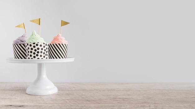 Cupcakes sur l'affichage avec le drapeau d'or Photo gratuit