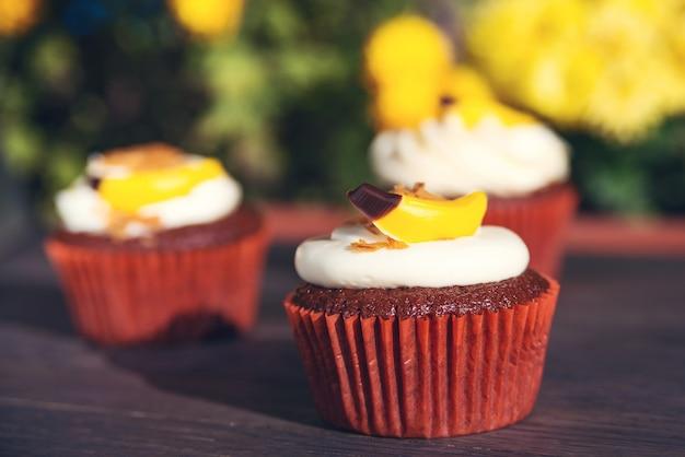 Cupcakes à La Crème Et Aux Bonbons. Délicieux Petits Gâteaux De Pâques Sur Table. Délicieux Petits Gâteaux Au Chocolat. Carte De Vacances De Pâques. Photo Premium