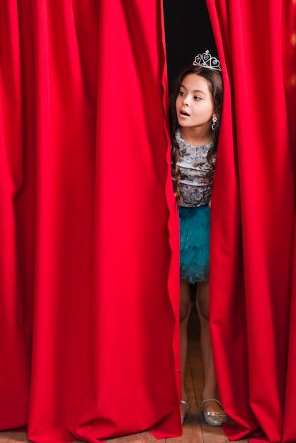 Curieuse jolie fille furtivement du rideau rouge sur scène Photo gratuit
