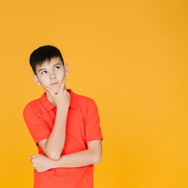 Curieux jeune garçon en levant Photo gratuit
