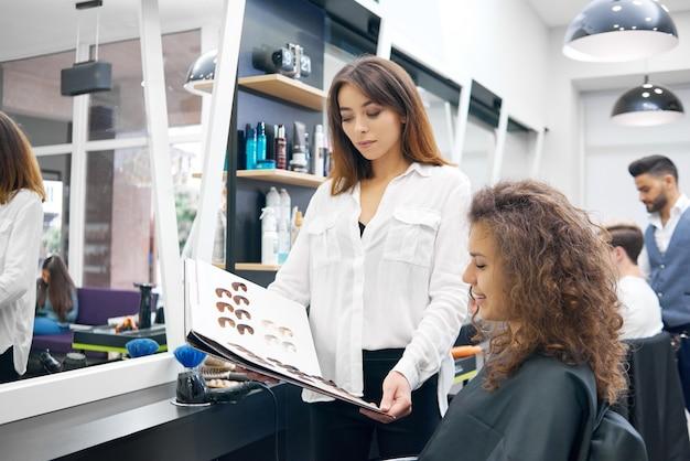 Curly, jeune fille, cueillette des couleurs pour la tonification des cheveux, assis dans le salon beaty. Photo Premium