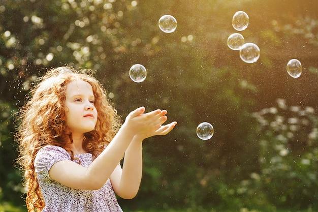 Curly petite fille attraper un bulles de savon. Photo Premium