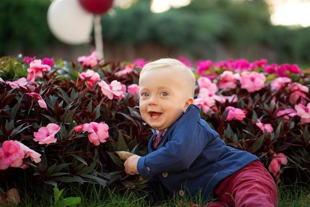 Cute espiègle sourit blond. garçon de 1 ans assis sur l'herbe verte en dehors de jouer avec un ballon. Photo Premium