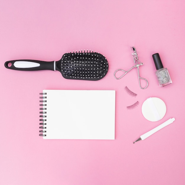 Cuticule; brosse à cheveux; éponge; faux cils; recourbe-cils; bouteille de vernis à ongles avec bloc-notes en spirale vierge sur fond rose Photo gratuit