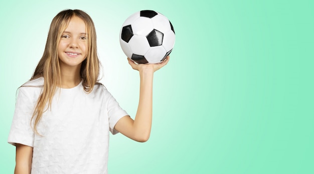 Cutie petite fille en chemise blanche tenant un ballon de football dans les mains Photo Premium